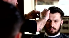 Barber performs a haircut with scissors and combs his client. Client while Stock Footage