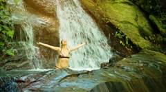 Young woman bathing in a natural waterfall in the rainforest Stock Footage
