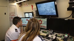 Paramedics observe disaster area with remote camera Stock Footage