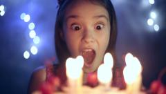 Birthday of the little girl she blows out candles on cake. Bokeh background - stock footage