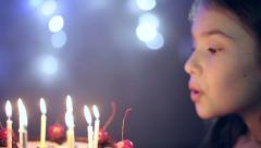 Birthday of the little girl she blows out candles on cake. Slow motion Stock Footage