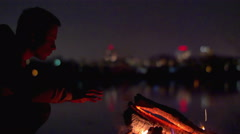 The man sit outdoor near the bonfire by city bokeh background, rest and relax Stock Footage