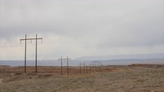 Large telephone poles running through a desert Stock Footage