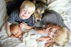 Three Happy Young Children Snuggling with Pet Dog in Bed - stock photo