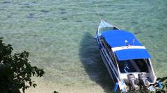 Motor tourist speed boat tied up at sea coast Stock Footage