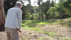 Senior Elderly Man Stands up from Bench and Walks with a Cane in Park - stock footage
