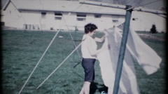 1966 - woman hangs laundry & talks to neighbor - vintage film home movie Stock Footage