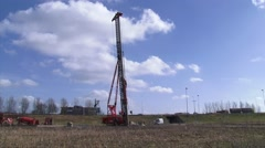 Pile driving machine hammering steel tubular foundation pile - long shot Stock Footage