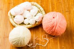 Roll of white and pink soft knitting yarn and wattled plate with zephyr Stock Photos