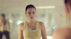 Purposeful girl trains in the hall in front of the mirror Stock Footage