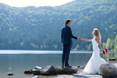 Beautiful married couple acting very romantic near a lake. Stock Photos