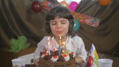 Young beautiful girl blowing candles on a birthday cake, slow motion Stock Footage