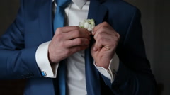 The groom wears a tie and cufflinks boutonniere - stock footage