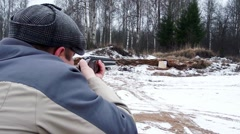 Hunter shoots a gun in the forest in winter. Stock Footage