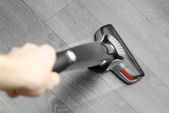 cleaning floor with cordless vacuum cleaner - stock photo