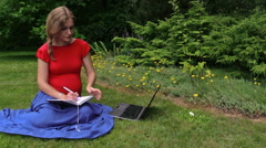 Woman look for info about pregnancy in laptop, note down to book Stock Footage