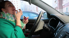 Young Caucasian woman coloring lips with lipstick while preparing to drive car Stock Footage