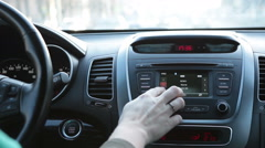 Human driving car and pushing buttons on radio, dashboard and wheel - stock footage