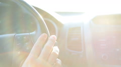 Dashboard and car wheel with human arm on it in sun light - stock footage