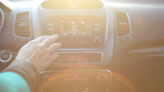 Woman hand turning on radio on car dashboard in sunny day - stock footage