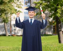 Stock Photo of smiling adult student in mortarboard with diploma