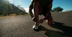 African American runner tying his shoelaces Stock Footage