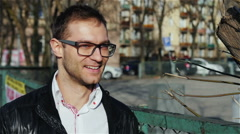 Portrait of young man wearing eye glasses walking in the city streets. Stock Footage