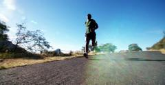 Slow motion shot of athlete sprinting along road outdoors Stock Footage