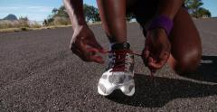 African American runner tying his laces, close up slow motion Stock Footage