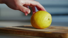 Slicing lemon on a wooden cutting board 4K - stock footage