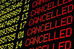 Cancelled flights on airport board - stock photo