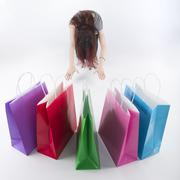 Woman Bowing on Floor In Front of Shopping Bags - stock photo