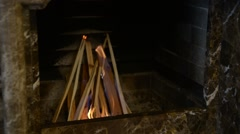 Burning wood in a fireplace , a man pours lighter fluid Stock Footage