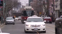 Streetcars in a city streetscape, downtown with traffic and people. Stock Footage