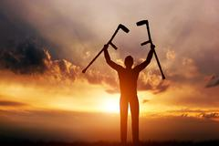 A disabled man raising his crutches at sunset. Cure, medical miracle. - stock illustration