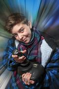 concentrated teenage boy with joy-stick with motion blur background - stock photo