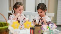 Two girls painting Easter eggs Stock Footage