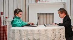 One girl is sitting at the computer the second reading a book Stock Footage