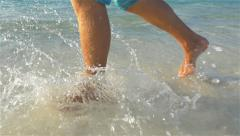SLOW MOTION CLOSEUP: Running and splashing in shallow sea water - stock footage