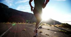 Running feet of male runner on mountain road in slow motion Stock Footage