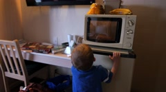 Toddler watching pizza cook in hotel microwave Stock Footage