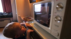 A family cooking frozen pizza in hotel microwave Stock Footage