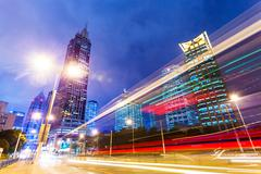 Traffic trails and office buildings in modern city. Stock Photos