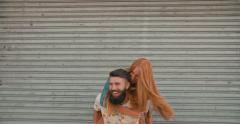 Redhead girl laughing loudly while hipster boyfriend piggyback Stock Footage