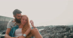 Retro couple laughing together while sitting on rocks at seaside Stock Footage