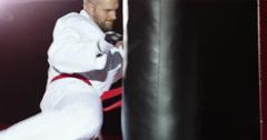 A young athlete in kimono kicks a bag. Stock Footage
