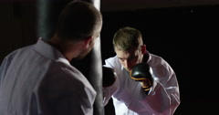 Trainer with a young athlete practicing with a punching bag - stock footage