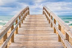 A wide wooden boardwalk leads to an ocean beach beneath dramatic clouds. Stock Photos