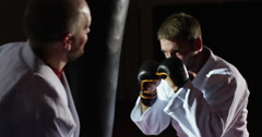 Trainer with a young athlete practicing with a punching bag. Stock Footage
