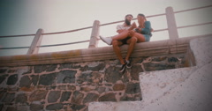 Happy retro hipster couple laughing together on wall Stock Footage